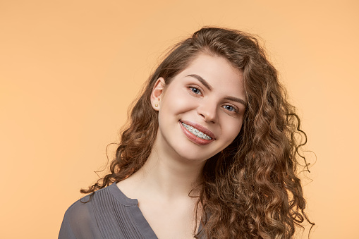 a smiling woman with ceramic braces from Dr. Amy James and Associates Orthodontists